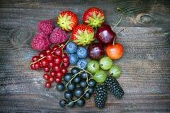 Stiger ombord lösa bärfrukter för sommar på tappning stilleben fotografering för bildbyråer