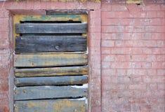 Stigit ombord upp fönster på en gammal tegelstenvägg Royaltyfri Foto
