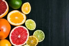 Stihli frais d'agrume Citrons, chaux, pamplemousse et orange sur un fond noir Photos stock