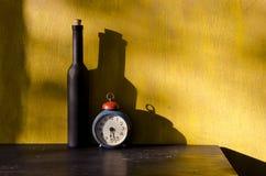 Stiil-vida con la botella negra y el reloj viejo Fotos de archivo