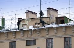 Stijg de sneeuw en de ijskegels van het dak op Het werkende schoonmakende werk zonder verzekering Rusland, St Petersburg stock afbeelding