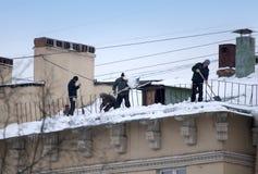 Stijg de sneeuw en de ijskegels van het dak op Het werkende schoonmakende werk zonder verzekering Rusland, St Petersburg royalty-vrije stock foto