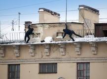Stijg de sneeuw en de ijskegels van het dak op Het werkende schoonmakende werk zonder verzekering Rusland, St Petersburg stock afbeeldingen