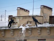 Stijg de sneeuw en de ijskegels van het dak op Het werkende schoonmakende werk zonder verzekering Rusland, St Petersburg royalty-vrije stock foto's