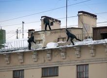 Stijg de sneeuw en de ijskegels van het dak op Het werkende schoonmakende werk zonder verzekering Rusland, St Petersburg stock foto