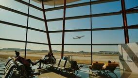Stijg het vliegtuig in de vensters van de luchthaven op stock fotografie