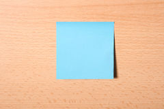Stiky paper. Blue sticky paper on wooden background Royalty Free Stock Photos
