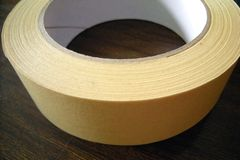 Stiky tape. Yellow sticky tape on brown table Royalty Free Stock Photo