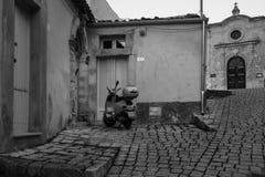 Stil cobbled straat in Italië met een uitstekende geparkeerde autoped stock fotografie