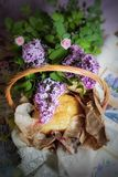 Stil life. Bread packed in kraft paper ribbon and napkin with embroidery in a wicker basket adorned with lilac branches and pink roses   from above Royalty Free Stock Photos