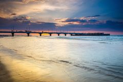 Stil strand met pijler bij zonsondergang, stock afbeeldingen