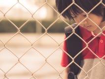 Stile d'annata del ragazzo triste dietro il reticolato della maglia del recinto fotografia stock libera da diritti
