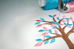 Stile del fumetto dell'albero del ricamo sul tessuto di cotone bianco immagine stock