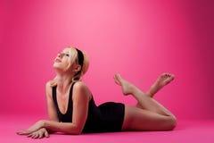 Stile del perno-in su di sport della donna di bellezza sul colore rosa Fotografia Stock