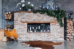 Stile del sottotetto Interno con il camino del mattone, candele, pianta, pelle moderna delle mucche, parete grigia, firewoods, pr fotografie stock libere da diritti