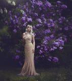 Stile della primavera Bella bionda sensuale della ragazza in primavera Giardino sbocciante della sorgente Ragazza in un vestito e fotografia stock