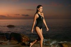 Stile della spiaggia di estate Donna in costume da bagno nero che cammina alla costa di mare immagine stock libera da diritti