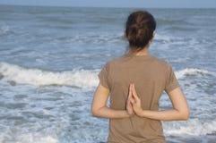 Stile di vita asiatico di tramonto della spiaggia di yoga della ragazza immagini stock libere da diritti