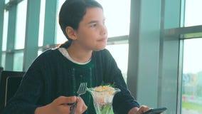 Stile di vita aspettante dell'aeroporto un volo in aereo La ragazza teenager mangia l'insalata e guarda lo smartphone Internet in archivi video