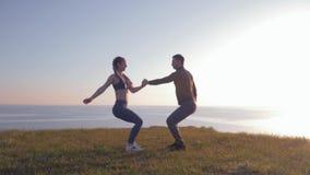 Stile di vita attivo, coppie atletiche tenentesi per mano insieme ed accovacciantesi simultaneamente alla natura archivi video
