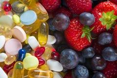 Stile di vita, concetto di dieta, frutta e pillole sani, supplementi della vitamina con su fondo bianco Fotografie Stock