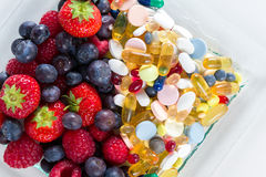 Stile di vita, concetto di dieta, frutta e pillole sani, supplementi della vitamina con su fondo bianco Fotografia Stock