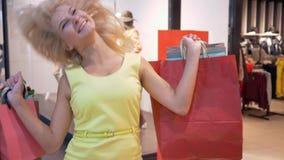 Stile di vita del cliente, donna allegra con il lotto dei pacchetti di acquisto dopo che acquisti in depositi costosi nella vendi stock footage