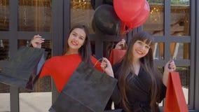 Stile di vita del cliente, ragazze alla moda divertendosi i nuovi acquisti dal deposito nella stagione degli sconti a venerdì ner archivi video