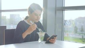 Stile di vita dell'aeroporto che aspetta un volo in aereo La ragazza teenager mangia l'insalata e guarda lo smartphone Internet i archivi video
