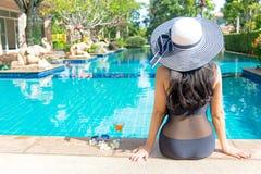 Stile di vita delle donne che si rilassa vicino al sunbath di lusso della piscina, giorno di estate alla stazione balneare nell'h Immagini Stock Libere da Diritti
