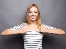 Stile di vita e concetto della gente: Donna felice che dà pollice su Fotografia Stock