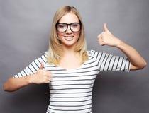 Stile di vita e concetto della gente: Donna felice che dà pollice su Immagine Stock