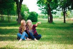Stile di vita e concetto della gente: Due amici di ragazza che si siedono insieme e che si divertono fotografia stock