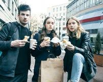 Stile di vita e concetto della gente: due ragazze e tipo che mangiano alimenti a rapida preparazione sulla via che si diverte ins fotografia stock
