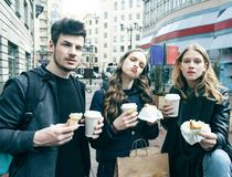 Stile di vita e concetto della gente: due ragazze e tipo che mangiano alimenti a rapida preparazione sulla via che si diverte ins immagine stock libera da diritti