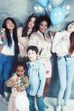 Stile di vita e concetto della gente: giovane donna graziosa di nazioni di diversit? con differenti bambini di et? che celebrano  fotografie stock libere da diritti