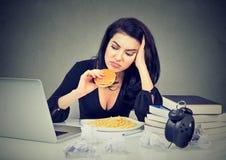 Stile di vita e concetto sedentari degli alimenti industriali Donna sollecitata che si siede allo scrittorio che mangia hamburger Immagine Stock