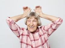 Stile di vita, emozione e concetto della gente: Nonna invecchiata con il fronte colpito Ritratto della nonna con la camicia rosa fotografia stock libera da diritti