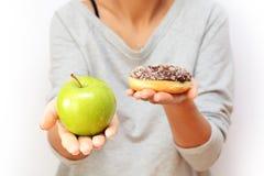 Stile di vita o concetto sano di nutrizione con la tenuta della giovane donna in mani una mela verde e una ciambella immagine stock libera da diritti