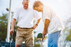 Stile di vita pensionato delle coppie senior che giocano mini golf fotografie stock libere da diritti