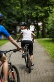Stile di vita sano - biciclette di guida della gente nel parco della città Immagine Stock Libera da Diritti