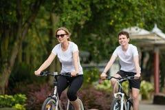 Stile di vita sano - biciclette di guida della gente nel parco della città Fotografia Stock