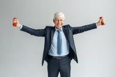 Stile di vita sano Condizione dell'uomo d'affari sull'esercitazione grigia con sorridere delle mani delle teste di legno da parte immagine stock