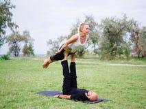 Stile di vita, sport e concetto della gente: Giovani coppie nella posa di yoga Immagini Stock Libere da Diritti