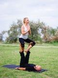 Stile di vita, sport e concetto della gente: Giovani coppie nella posa di yoga Immagine Stock Libera da Diritti