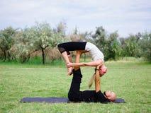 Stile di vita, sport e concetto della gente: Giovani coppie nella posa di yoga Fotografia Stock