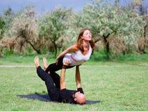 Stile di vita, sport e concetto della gente: Giovani coppie nella posa di yoga Fotografie Stock