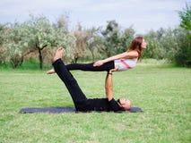 Stile di vita, sport e concetto della gente: Giovani coppie nella posa di yoga Fotografie Stock Libere da Diritti