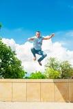 Stile di vita sportivo attivo Uomo di salto atletico Backgrou del cielo blu Fotografia Stock