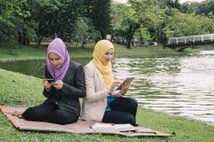 Stile di vita di tecnologia e di urbano, giovane muslimah che si siede su un'erba verde al parco Fotografie Stock